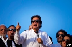 FILE - Pakistan's cricketer-turned-politician Imran Khan, center, is surrounded by aides as he addresses to his supporters near the parliament building in Islamabad, Pakistan, Aug. 27, 2014.