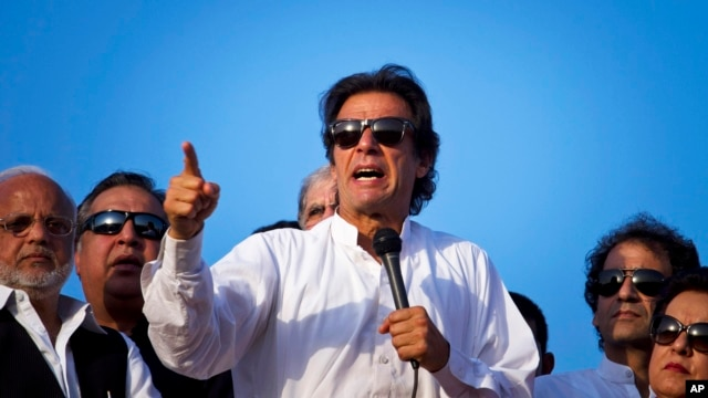 Pakistan's cricketer-turned-politician Imran Khan, center, is surrounded by aides as he addresses supporters near the parliament building in Islamabad, Aug. 27, 2014.