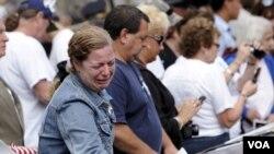 Seorang perempuan tersedu-sedan menatap ukiran nama sanak keluarganya di monumen peringatan 11 September (11/9).