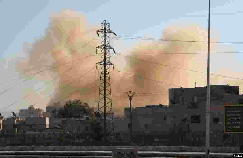 Smoke rises at a site hit by what activists said was a barrel bomb dropped by forces loyal to Syria's President Bashar al-Assad in Aleppo, Feb. 12, 2014.