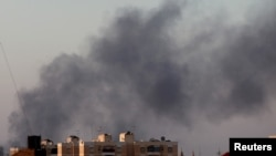 Black smoke marks where clashes are taking place between pro-government forces and an alliance of anti-Moammar Gadhafi rebels who have joined forces with the Islamist group Ansar al-Sharia in Benghazi, Libya, Aug. 15, 2015.