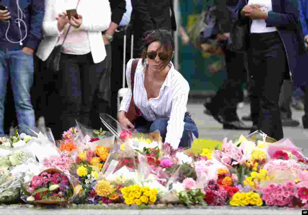 A woman places flowers on a floral tribute in the London Bridge area of London, June 5, 2017.