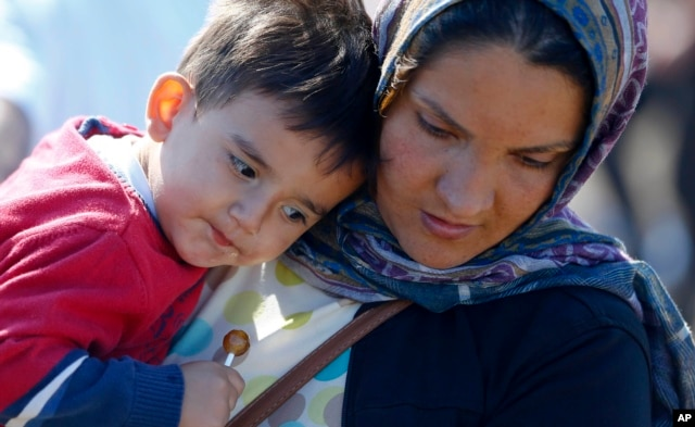 A Syrian woman carries a child as she arrives near the Hungarian border with Serbia, in Roszke, southern Hungary, Sept. 9, 2015.