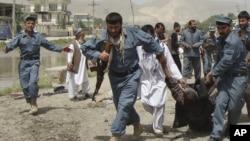阿富汗警察在巴格兰省议会大楼外的自杀炸弹袭击现场抬走伤员。(2013年5月20日)