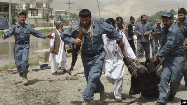 Afghan policemen evacuate a wounded person after a suicide bomber struck outside a provincial council headquarters in Pul-i-Khumri, Baghlan province, northern Afghanistan, May 20, 2013.