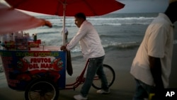 A vendor of seafood cocktails pushes his cart along the shore in Cartagena, Colombia, Tuesday. Colombia's government and the Revolutionary Armed Forces of Colombia, FARC, signed on Monday a peace agreement to end over 50 years of conflict.