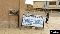 ຄົນຢ່າງຜ່ານປ້າຍ ທີ່ໝາຍສະຖານທີ່ມູນມໍລະດົກໂລກ ທີ່ເມືອງ Timbuktu ຂອງມາລີ.