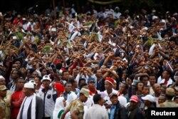 FILE - Demonstrators chant slogans while flashing the Oromo protest gesture during Irreecha, the thanksgiving festival of the Oromo people, in Bishoftu town, Oromia region, Ethiopia, Oct. 2, 2016.