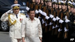 Philippine President Rodrigo Duterte, right, walks with Russian Rear Adm. Eduard Mikhailov, Deputy Commander of Flotilla of Pacific Fleet of Russia, during arrival honors as he visits the Russian anti-submarine Navy vessel Admiral Tributs in Manila.