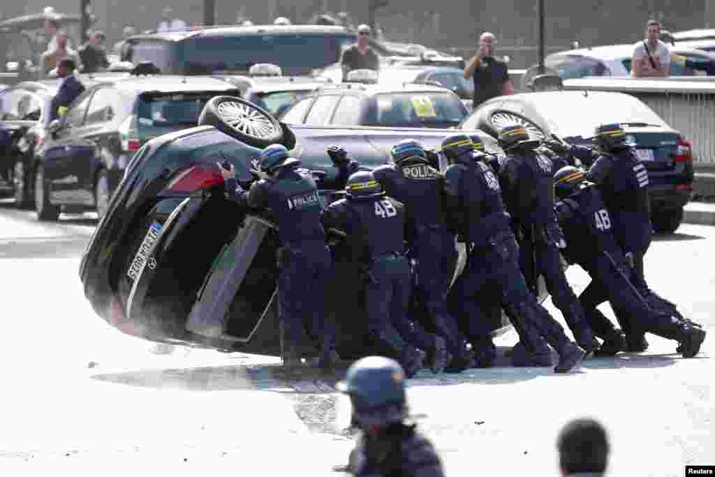 French riot police push an overturned car as striking French taxi drivers demonstrate at the Porte Maillot to block the traffic on the Paris ring road during a national protest against car-sharing service Uber, in Paris.