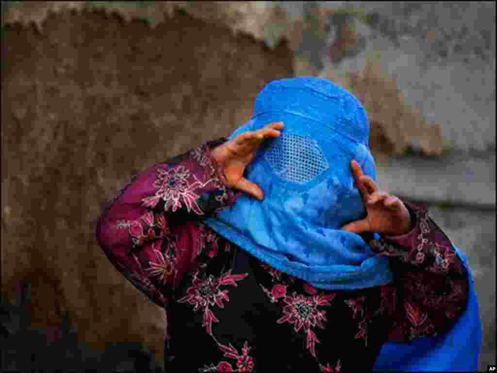 افغانستان کے شہر کابل میں ایک بچی برقع کی جالی سے باہر دیکھ رہی ہے