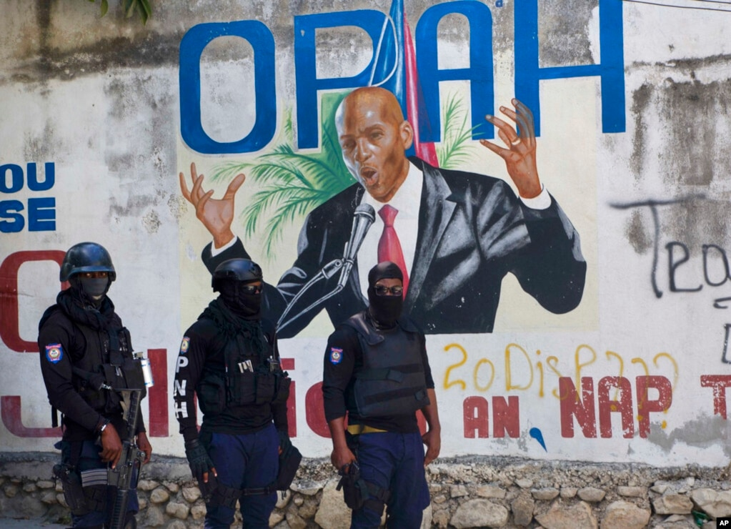 La police se tient près d'une peinture murale représentant le président haïtien Jovenel Moise, près de la résidence du dirigeant où il a été tué par des hommes armés aux premières heures du matin à Port-au-Prince, Haïti, mercredi 7 juillet 2021.