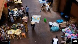 En plein centre d'un marché de Ouagadougou, Burkina Faso, un homme, au centre, arbore une carte avec le continent africain mardi 4 novembre 2014. Des émissaires internationaux ont tenté mardi de résoudre la crise politique au Burkina Faso, avec le spectre d'un vide de pouvoir imminent après la chute du président Blaise Compaoré qui a fait 27 ans au pouvoir. (AP Photo / Theo Renaut)