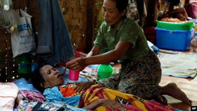 A family member takes care of a HIV patient at HIV/AIDS care center founded by Phyu Phyu Thin, a parliament member of Burma's Opposition Leader Aung San Suu Kyi's NLD Party, in outskirts of Rangoon, Mar. 1, 2014.