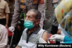 Inan Rustandi, 72 tahun, warga Desa Sindanglaya, bereaksi saat menerima dosis pertama vaksin Sinovac Biotech, Jawa Barat, 15 Juni 2021. (Foto: REUTERS/Willy Kurniawan)