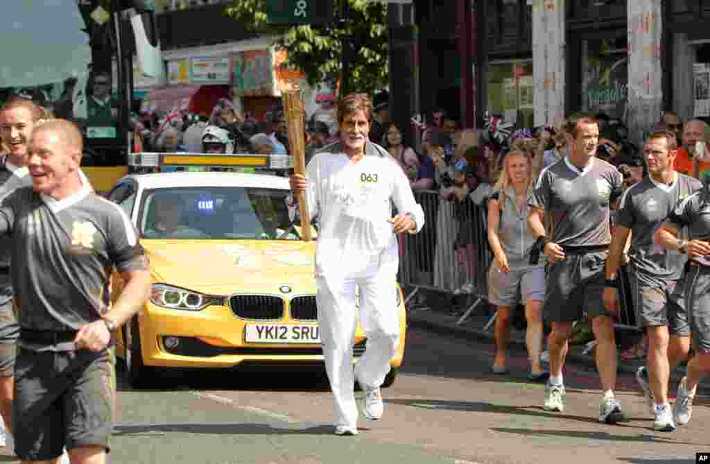 Bollywood actor Amitabh Bachchan carries the Olympic flame on the torch relay leg between The City of London and the borough of Southwark in London, July 25, 2012. (Photo provided by LOCOG)