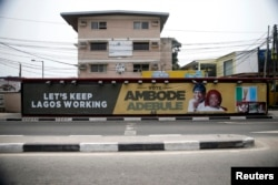 A campaign banner in support of the opposition All Progressives Congress (APC) governorship candidate Akinwunmi Ambode and his running mate, Oluranti Adebule, is seen along a road in Ikoyi district in Lagos, Feb. 13, 2015.