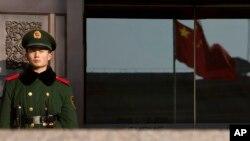 Seorang polisi tengah berjaga di pintu masuk sebuah gedung Pemerintah China di Beijing (Foto: dok). Sekitar 30 aktivis dan orang-orang yang mengajukan petisi menuntut kebebasan pembangkang Cao Shunli, ditahan hari Senin (24/2) setelah berkunjung ke sebuah rumah sakit di Beijing.
