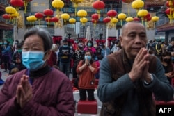 People wear masks as they pray at Wong Tai Sin temple on the first day of the Lunar New Year in Hong Kong, Jan. 25, 2020, as a preventative measure following a coronavirus outbreak that began in Wuhan, China.