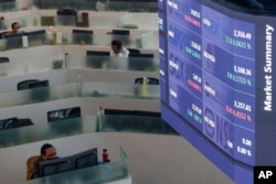 Traders wearing protective masks to prevent the spread of the coronavirus work beside an electronic board showing morning market summaries at the Philippine Stock Exchange in Taguig, Philippines, Wednesday, Nov. 4, 2020, as investors await for…