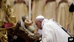 Đức Giáo hoàng Phan Xi Cô hôn vào tượng Chúa Hài Đồng Giêsu trong khi Ngài cử hành Thánh lễ Đêm Giáng inh tại Vatican hôm 24/12.