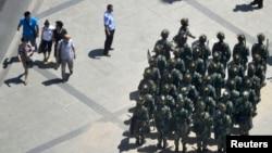 2013年6月30日,日本共同社的照片顯示中國武裝警察在新疆維吾爾族自治區烏魯木齊進行一次鎮壓騷亂行動。