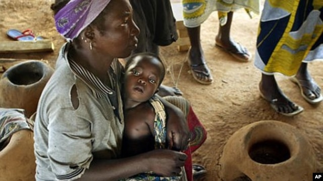 Abdou Sawadogo, 3, is held by his mother as he waits to be given medicine by Red Cross workers at the Nicla II refugee camp, which houses people who have been driven from their land, in Guiglo in western Ivory Coast (File Photo)