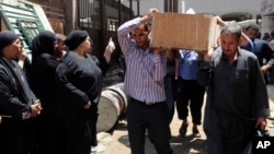 Egyptians remove a body for burial from the Zenhoum morgue in Cairo, August 19, 2013.
