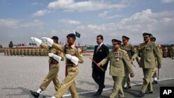 Pakistan's Prime Minister Yusuf Raza Gilani (C, rear) reviews an honor guard during a passing out ceremony in Quetta October 11, 2011