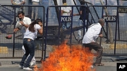 People take cover as police clash with dozens of stone-throwing Kurdish protesters at a peace rally that turned violent in Istanbul, Turkey, September 1, 2011.
