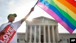 Carlos McKnight of Washington, waves a flag in support of gay marriage outside of the Supreme Court in Washington, D.C., June 26, 2015.