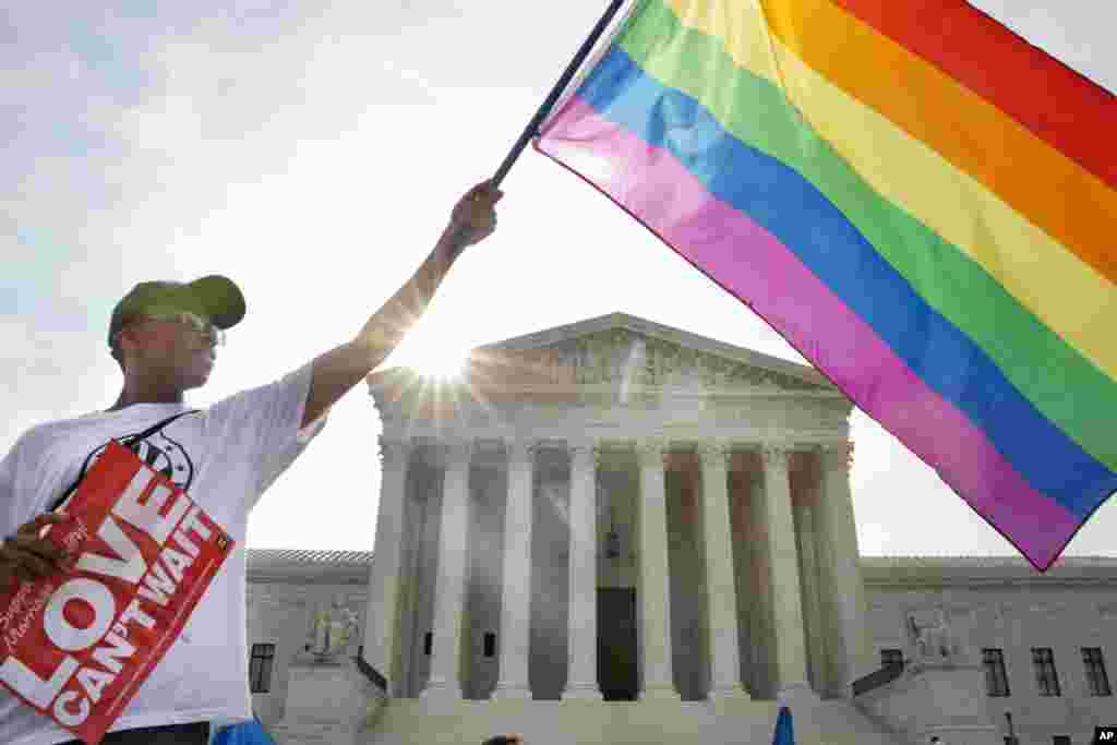 Carlos McKnight waves a flag in support of gay marriage outside of the Supreme Court in Washington, D.C. The Court on Friday declared same-sex couples have a right to marry anywhere in the country, essentially invalidating laws in some states barring same-sex marriage.