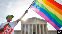 FILE - Carlos McKnight of Washington waves a flag in support of gay marriage outside of the Supreme Court in Washington, D.C., June 26, 2015.
