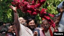 Ông Amit Shah, một nhà lãnh đạo của đảng BJP ném các vòng hoa về hướng những người ủng hộ sau khi nghe kết quả bầu cử bên ngoài trụ sở đảng trong thủ đô New Delhi, 16/5/14
