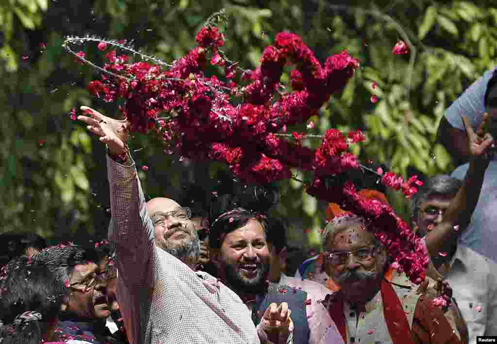 Amit Shah, a senior leader of the Bharatiya Janata Party (BJP), throws garlands towards BJP supporters during celebrations after learning of poll results outside the party headquarters, in New Delhi, May 16, 2014.