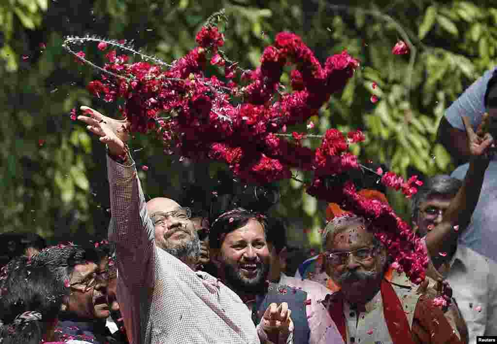 Amit Shah, um líder sénior do Partido do Povo ouBharatiya Janata Party (BJP), atira coroas de flores aos apoiantes do BJP, durante os festejos depois de serem conhecidos os resultados das eleições, na sede do partido, Nova Deli, Maio 16, 2014.
