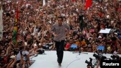 Joko Widodo sebagai calon presiden dalam kampanye pilpres 2014, berlari di panggung setelah berpidato di depan pendukungnya di Gelora Bung Karno, 5 Juli 2014. (Foto:dok).