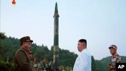 김정은 북한 국무위원장(가운데)이 새로 개발한 정밀유도 탄도미사일 시험발사를 참관했다고, 관영 조선중앙통신이 지난해 5월 보도했다. 김 위원장 뒤로 미사일 발사대 모습이 보인다.