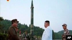 김정은 북한 국무위원장(가운데)이 새로 개발한 정밀유도 탄도미사일 시험발사를 참관했다고, 관영 조선중앙통신이 지난 5월 보도했다. 김 위원장 뒤로 미사일 발사대 모습이 보인다.