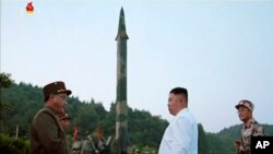 FILE - This image made from video of an undated still image broadcasted in a news bulletin on May 30, 2017, by North Korea's KRT shows North Korean leader Kim Jong Un and a missile launcher in North Korea.
