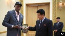 북한을 방문 중인 전 미 프로농구 선수 데니스 로드먼이 15일 김일국 북한 체육상에게 도널드 트럼프 미국 대통령의 저서 '거래의 기술'을 건네고 있다.