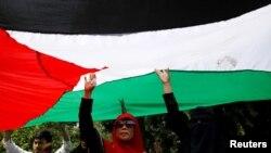 Demonstran memegang bendera Palestina dalam demonstrasi di depan Kedutaan Besar Amerika di Jakarta, untuk mengecam keputusan AS mengakui Yerusalem sebagai Ibu Kota Israel, 8 Desember 2017.