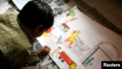 FILE - An Indian boy sketches a painting in a classroom at a boys' welfare home in New Delhi.
