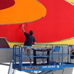 "Stephan Ackermann works on ""Coming Home (Meet Me) At the Waterfall"" by his brother, artist Franz Ackermann, at Cowboys Stadium in 2009"