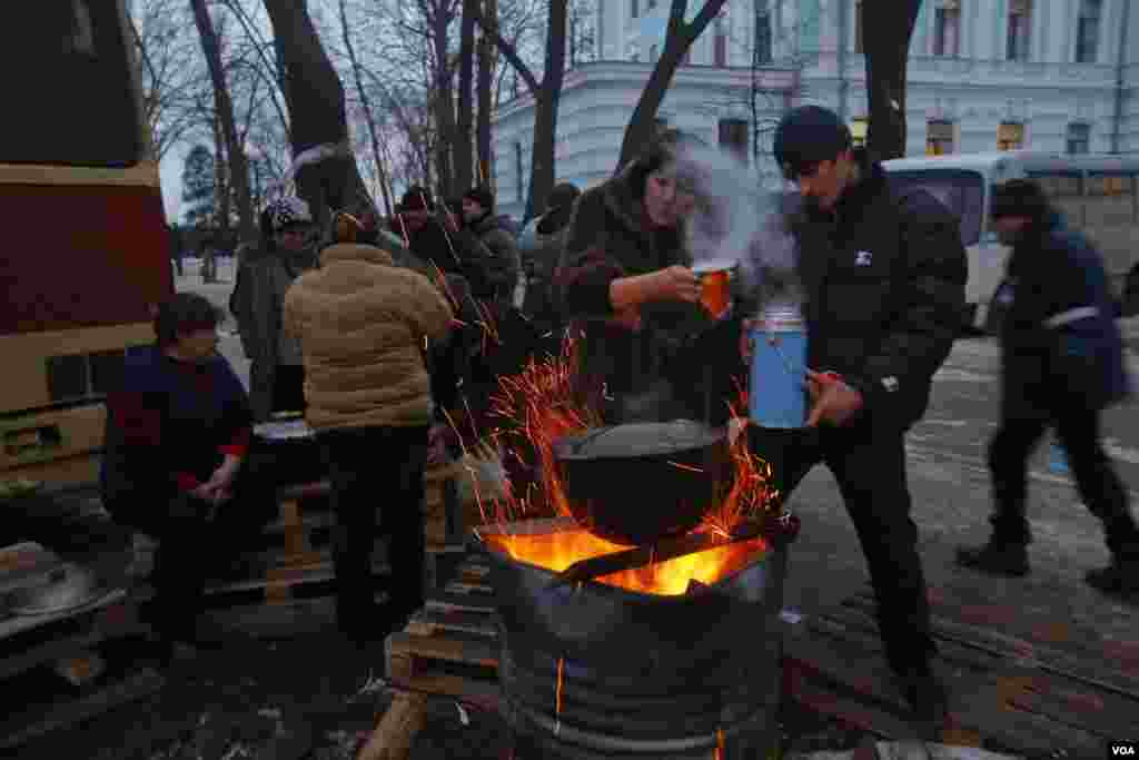 Supporters of President Yanukovych's party of Regions drink hot tea near a fire as they gather during a rally in Kyiv, Ukraine, Dec. 15, 2013.