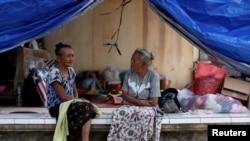 Dua perempuan lansia tengah berbincang di tenda evakuasi sementara di dekat Gunung Agung, kawasan Manggis, Bali, 1 Oktober 2017. (REUTERS/Darren Whiteside)