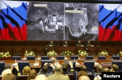Defense Ministry officials sit under screens with satellite images on display during a briefing in Moscow, Dec. 2, 2015.
