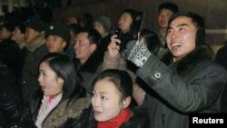 지난해 1월 평양 시민들이 새해맞이 불꽃축제에서 휴대전화로 사진을 찍고 있다.