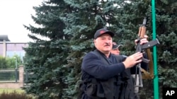 This image made from video provided by the State TV and Radio Company of Belarus, shows Belarus President Alexander Lukashenko armed with a Kalashnikov-type rifle near the Palace of Independence in Minsk, Belarus, Sunday, Aug. 23, 2020.
