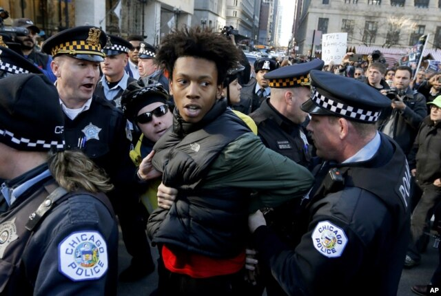 FILE - Lamon Reccord is taken into custody by Chicago police officers during a march calling for Chicago Mayor Rahm Emanuel and Cook County State's Attorney Anita Alvarez to resign, Dec. 9, 2015.